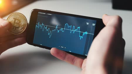 a man checking stock market on smartphone with btc bitcoin Wideo