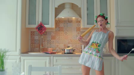 funny woman cook dance and sing with rolling pin while cooking in kitchen at home Wideo