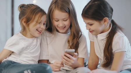 nurture : Beautiful little girls are sitting on the couch and showing her something interesting and funny on the smartphone
