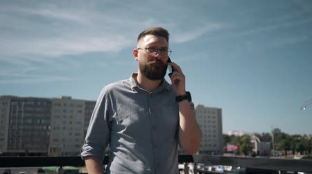 Handsome young bearded man walk and speaks on the phone at the city Wideo