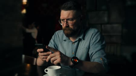 Handsome young bearded man looks into the phone and drink cofee in the cafe