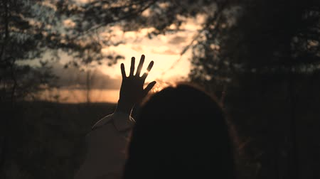 Girl looks at the sun through her hand Wideo