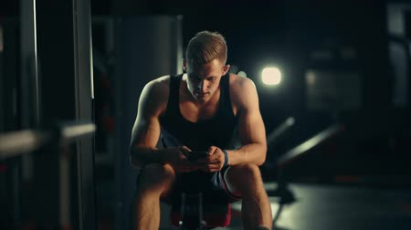 Muscular man looks into phone and smiles in dark gym, lifting weights