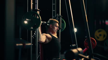 A muscular man doing exercises on the muscles of his shoulders raises the bar in a dark gym, lifting the weights Wideo