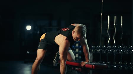 A muscular man performs dumbbell exercises on the back muscles in a dark gym, lifting weights Wideo