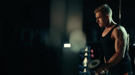разорвал : A muscular man performs exercises understands dumbbells for muscles of the biceps in a dark gym, lifting weights