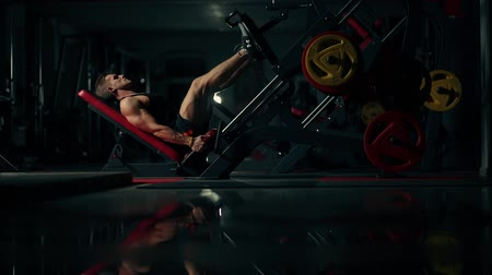 разорвал : A muscular man performs exercises on a sports training apparatus for leg muscles in a dark gym, lifting weights Стоковые видеозаписи