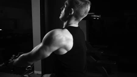 kordon : A muscular man performs exercises on the back muscles in a dark gym, lifting weights Stok Video