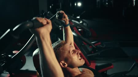 разорвал : Muscular man doing exercises on the muscles of the shoulders, heavy weight. Of the last strength. hard training
