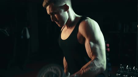 A muscular man doing exercises raises dumbbells on muscles of the biceps, heavy weight. hard training Wideo