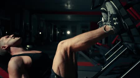 A muscular man performs exercises on a sports training apparatus for leg muscles in a dark gym, lifting weights Wideo