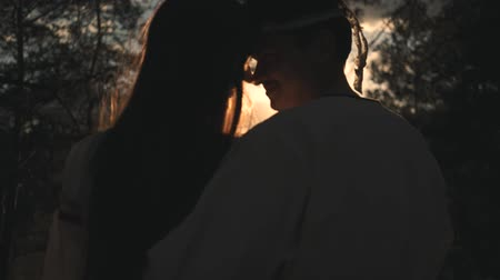 beijos : A loving couple in folk costumes hugs at sunset in the forest