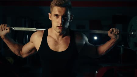 suplemento : muscular man in the gym training his legs quadriceps and hamstrings with a bar swap concept of fitness and bodybuilding Stock Footage