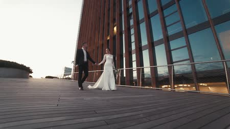 compromisso : Newly wed loving couple walk near a skyscraper Stock Footage