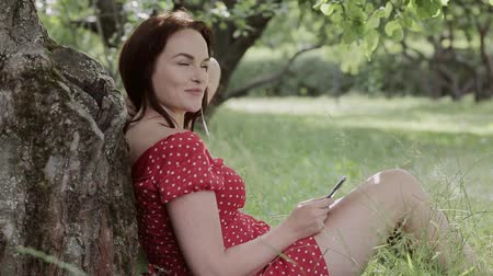 artı : Plus size girl sitting on grass under tree and using her smartphone