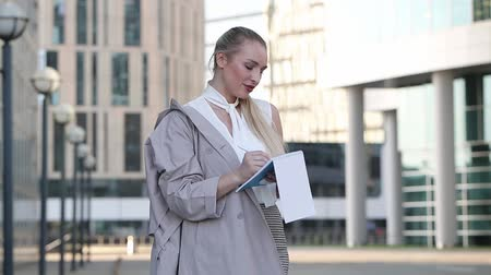 небоскреб : Young business woman writing in her notebook standing among the downtown
