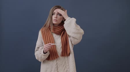 termometr : Sick girl wrapped in a warm scarf measures the temperature
