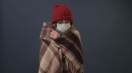 Sick woman wrapped in a blanket gets cold and feverish. Wideo