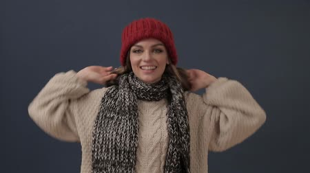 queda de neve : Beautiful young woman in scarf puts on hat and smiles