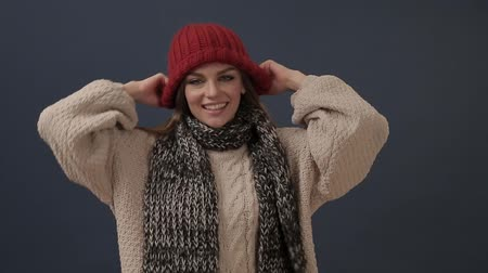 Beautiful young woman in scarf puts on hat and smiles
