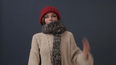 knitted : Beautiful young woman in scarf puts on hat and smiles