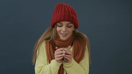 queda de neve : Beautiful young woman in scarf and hat drinking hot tea or mulled wine with orange