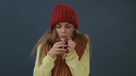 Beautiful young woman in scarf and hat drinking hot tea or mulled wine with orange