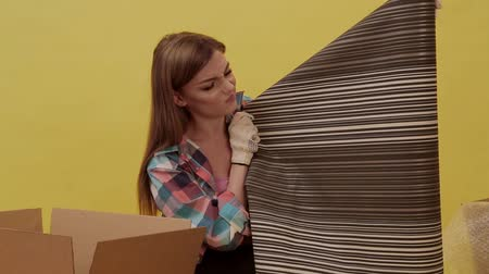A young woman moves and picks up wallpaper for repair Wideo