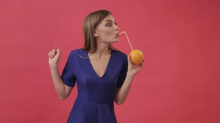 Beautiful girl in a dress drinking orange juice with a cocktail straw and dancing. Studio, purple background