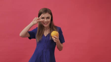 A beautiful girl in a dress connecting headphones to an orange and then dancing and listening to music. Studio, purple background