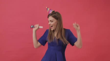 Positive woman in a birthday hat, blowing a party whistle. Studio, purple background