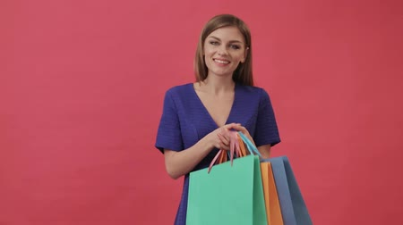Beautiful girl in a dress opening a package with gifts after shopping. Studio, pink background. Wideo