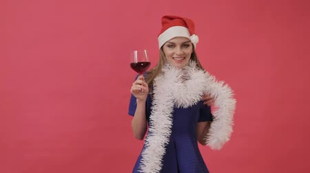 Beautiful girl in Christmas clothes dancing with a glass of wine in her hand. Studio, pink background.