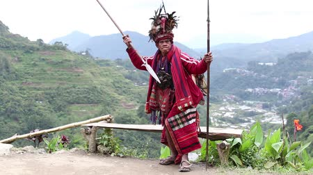hill tribe : BANAUE, PHILIPPINES - JANUARY 24, 2014 : Unknown old ifugao man in national dress next to rice terraces. Ifugao - the people in the Philippines. Refers to the mountain peoples. Stock Footage