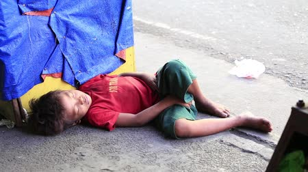 indigence : CEBU, PHILIPPINES - MARCH 15, 2014 : Poverty in Pholippines, a unidentified children sleeping on the street. Nearly one of every three Filipino children aged 4 to 10 is underweight .