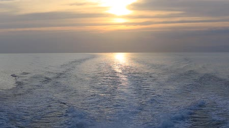 probudit : Blue ocean sea with fast yacht boat wake foam at sunset