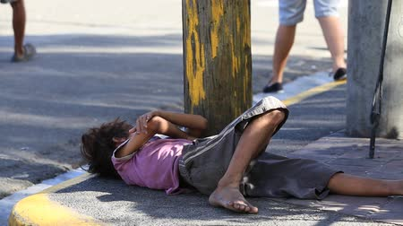 indigence : CEBU, PHILIPPINES - MARCH 15, 2014 : Poverty in Philippines, a unidentified boy sleeping on the street. Nearly one of every three Filipino children aged 4 to 10 is underweight Stock Footage