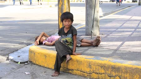 indigence : CEBU, PHILIPPINES - MARCH 15, 2014 : Poverty in Philippines, a unidentified beggar boys live on the street. Nearly one of every three Filipino children aged 4 to 10 is underweight. Stock Footage