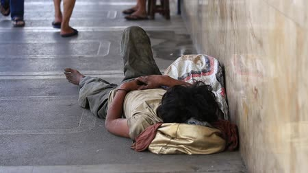 indigence : CEBU, PHILIPPINES - MARCH 15, 2014 : Poverty in Philippines, a unidentified beggar man sleeping on the street. Poverty and unemployment are high among uneducated people.