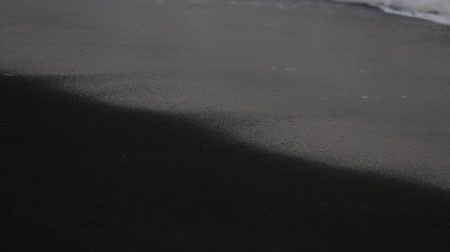 legazpi : Black volcanic sand and sea water waves on the beach in Legazpi, Philippines