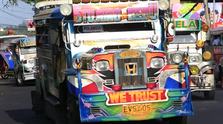 legazpi : LEGAZPI, PHILIPPINES - MARCH 17 2014: Jeepneys passing, Filipino inexpensive bus service. Jeepneys are the most popular means of public transportation in the Philippines. Stock Footage