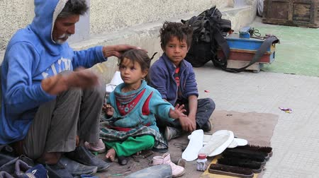 yoksulluk : LEH, INDIA - SEPTEMBER 08 2014: An unidentified beggar family begs for money from a passerby in Leh. Poverty is a major issue in India