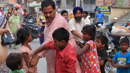 hobo : AMRITSAR, INDIA - SEPTEMBER 27, 2014: Unidentified poor children begging for money from a passerby in Amritsar near Golden temple. Poverty is a major issue in India