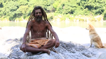 hobo : RISHIKESH, INDIA - OCTOBER 11, 2014 : Unidentified poor man sits on the ghat along the Ganges river. Poor Indians flock to Rishikesh for charity.