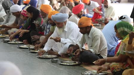 hacı : AMRITSAR, INDIA - SEPTEMBER 27, 2014: Unidentified indian people eating free food at a soup kitchen in the Golden Temple Stok Video
