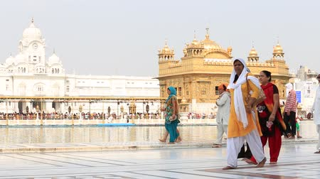 tapınaklar : AMRITSAR, INDIA - SEPTEMBER 27, 2014: Unidentified Sikhs and indian people visiting the Golden Temple in Amritsar, Punjab, India. Sikh pilgrims travel from all over India to pray at this holy site.