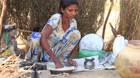 hobo : PUSHKAR, INDIA - OCTOBER 28, 2014: Unidentified Indian girl prepares chapati outdoor in Thar desert where the annual Pushkar Camel Mela. This fair is the largest camel trading fair in the world.