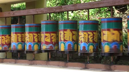 pneu : Buddhist religious prayer wheels in Tibetan monastery with written mantra in the Dharamsala near Dalai Lamas residence, India Stock Footage