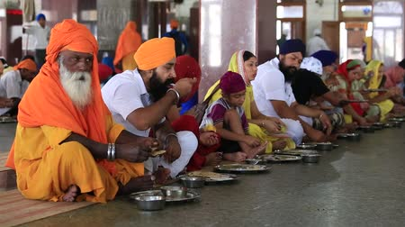 dobrovolník : AMRITSAR, INDIA - SEPTEMBER 27, 2014: Unidentified poor indian people eating free food at a soup kitchen in the Golden Temple Dostupné videozáznamy