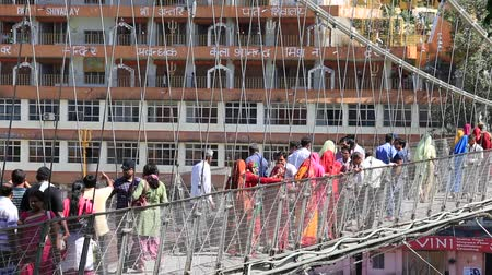 hobo : RISHIKESH, INDIA - OCTOBER 9, 2014 : Unidentified people crossing Laxman Jhula footbridge on river Ganga by the Tera Manzil Temple. Indian people flock to Rishikesh for charity.